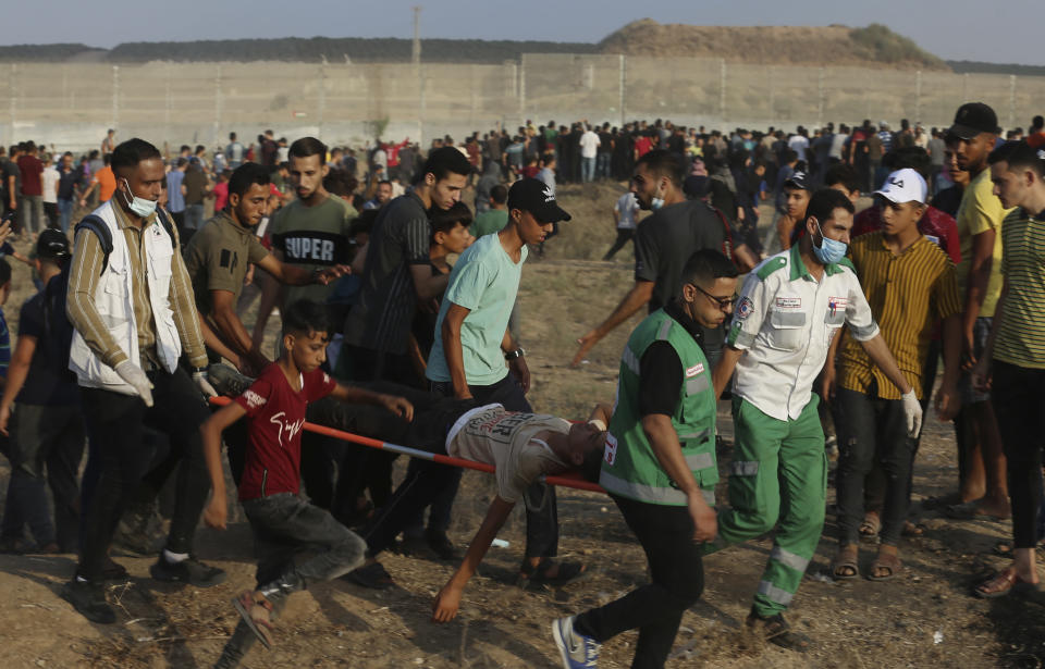 Medics evacuate a wounded person from the fence of Gaza Strip border with Israel, during a protest marking the anniversary of a 1969 arson attack at Jerusalem's Al-Aqsa mosque by an Australian tourist later found to be mentally ill, east of Gaza City, Saturday, Aug. 21, 2021. (AP Photo/Adel Hana)