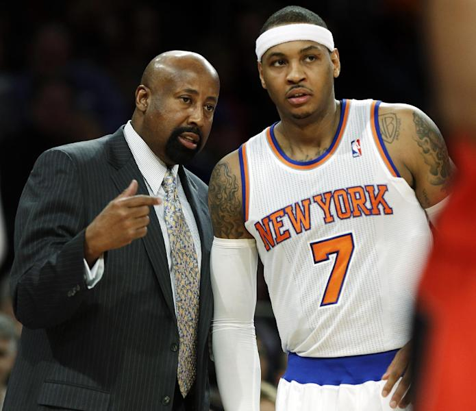 New York Knicks head coach Mike Woodson talks to Carmelo Anthony, right, during the first half of an NBA basketball game against the Toronto Raptors, Wednesday, Feb. 13, 2013, in New York. (AP Photo/Frank Franklin II)