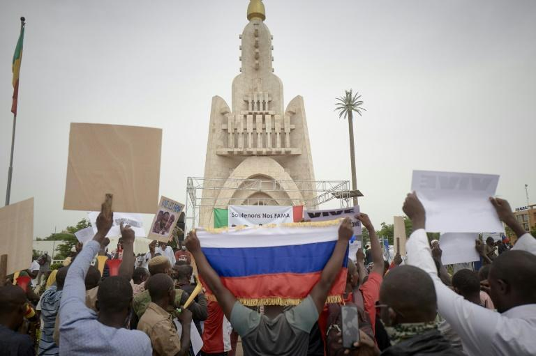 Coup supporters hold a Russian flag as they gather in Bamako's Independence square