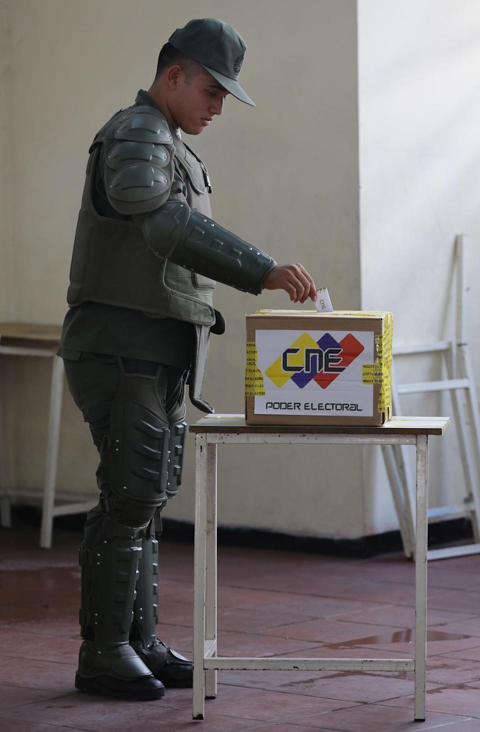 A soldier wearing protective gear casts his vote during municipal elections in Caracas, Venezuela, Sunday, Dec. 8, 2013. Venezuelans head to the polls to elect mayors and city councilors at a moment when the country's economic troubles have deepened, with inflation touching a two-decade high of 54 percent, and shortages of everything from toilet paper to milk spreading while the black market value of the currency plunges. (AP Photo/Ariana Cubillos)
