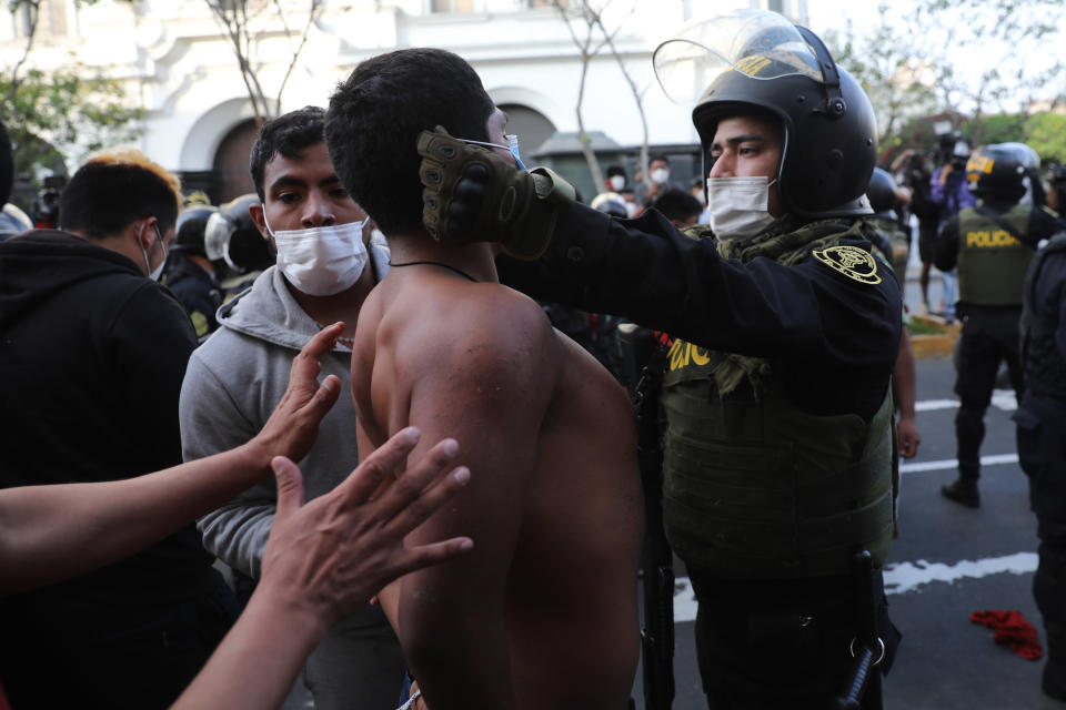 A police officer places a protective face mask on a protester who was detained near Congress where lawmakers swore-in a new president after voting to oust President Martin Vizcarra the day before, in Lima, Peru, Tuesday, Nov. 10, 2020. Peru swore in businessman and head of Congress Manuel Merino Tuesday who is unknown to most and was recently accused of trying to secure the military's support for a congressional effort to boot the nation's last leader out over unproven corruption allegations. (AP Photo/Rodrigo Abd)