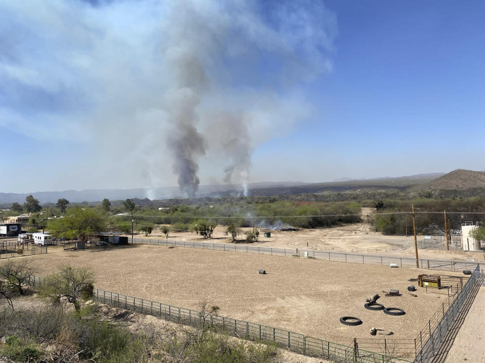 In this Friday, April 9, 2021. photo provided by Arizona Department of Forestry & Fire Management, the Pinal County Wildfire burns near rural properties in Dudleyville, Ariz. A small community in south-central Arizona remained under an evacuation notice Friday after crews and air tankers stopped the growth of a wildfire that burned at least 12 homes, officials said. (Arizona Department of Forestry & Fire Management via AP)