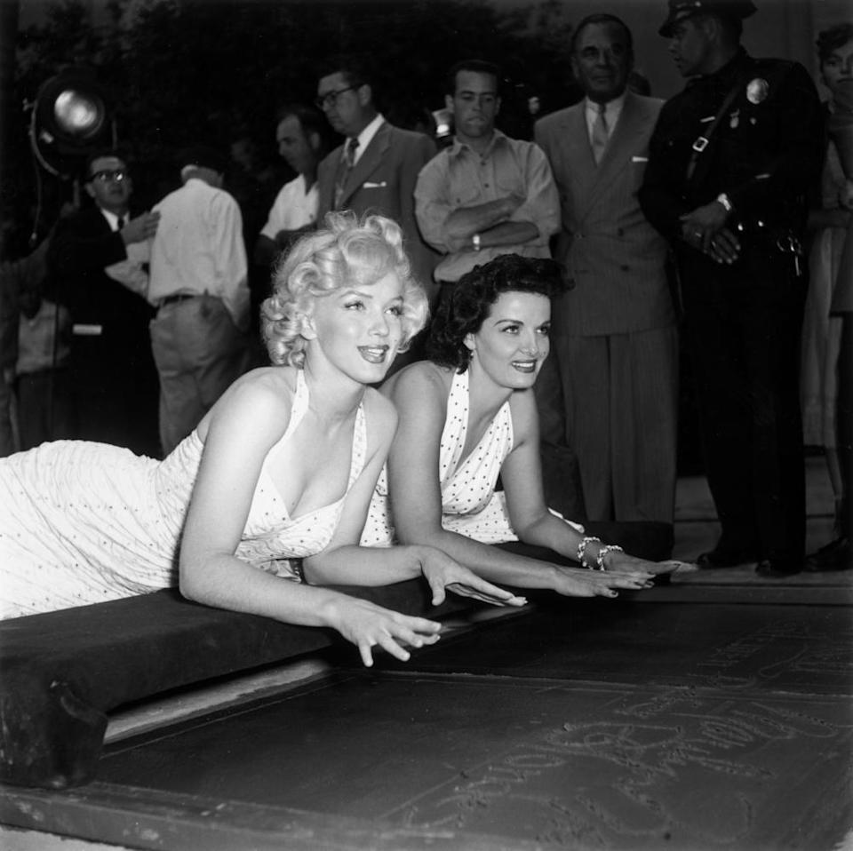 Marilyn Monroe and Jane Russell about to press their hands into wet cement at Grauman's Chinese theatre in Hollywood in 1953.