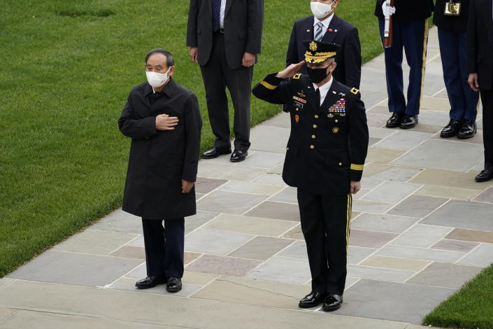 Japanese Prime Minister Yoshihide Suga at the Tomb of the Unknown Soldier for a wreath laying ceremony at Arlington National Cemetery in Arlington, Va., Friday morning, April 16, 2021, with U.S. Army Maj. Gen. Omar Jones. President Joe Biden will be welcoming Japan's prime minister to the White House on Friday in his first face-to-face meeting with a foreign leader, a choice that reflects Biden's emphasis on strengthening alliances to deal with a more assertive China and other global challenges. (AP Photo/Carolyn Kaster)