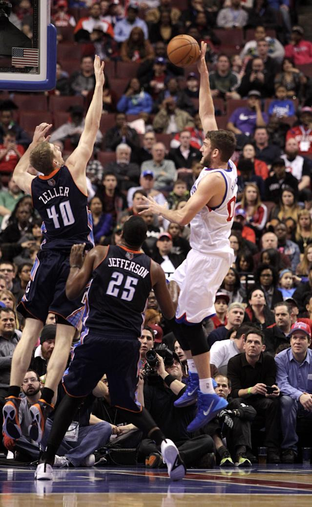 Philadelphia 76ers' Spencer Hawes (00), right shoots over Charlotte Bobcats' Cody Zeller (40) and Al Jefferson (25) in the first half of an NBA basketball game, Wednesday, Jan. 15, 2014 in Philadelphia. (AP Photo/H. Rumph Jr.)