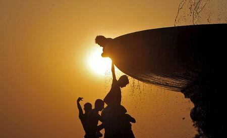 Boys cool off under a water fountain on a hot summer evening in New Delhi, India, April 25, 2016. REUTERS/Anindito Mukherjee