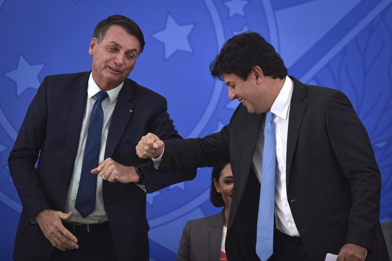 Brazil's President Jair Bolsonaro, left, greets his outgoing Health Minister Luiz Henrique Mandetta during the swearing-in ceremony for the new Health Minister Nelson Teich, not in picture, at Planalto palace in Brasilia, Brazil, Friday, April 17, 2020. Mandetta had garnered support for his handling of the pandemic that included promotion of broad isolation measures enacted by state governors, but had drawn the ire of Bolsonaro, who has said shutting down the economy would cause more damage than confining only high-risk Brazilians. (AP Photo/Andre Borges)