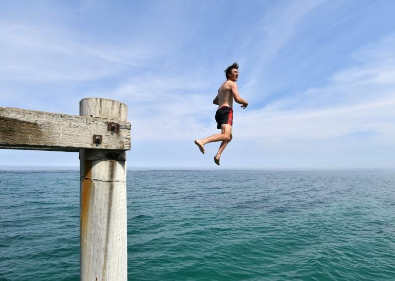 A swimmer jumps from the Port Noarlunga Jetty in Adelaide