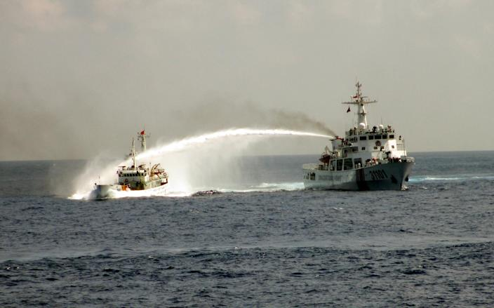 In this Sunday May 4, 2014 image made from video released by Vietnam Coast Guard, a Chinese coast guard vessel, right, fires water cannon at a Vietnamese vessel off the coast of Vietnam. China insisted Thursday, May 8, 2014 it had every right to drill for oil off Vietnam's coast and warned its neighbor to leave the area around the deep-sea rig where Chinese and Vietnamese ships are engaged in a tense standoff. With the ships jostling each other since China deployed the rig last weekend in disputed South China Sea waters, the United States warned both sides to de-escalate tensions and urged China to clarify its claims to the territory. (AP Photo/Vietnam Coast Guard)