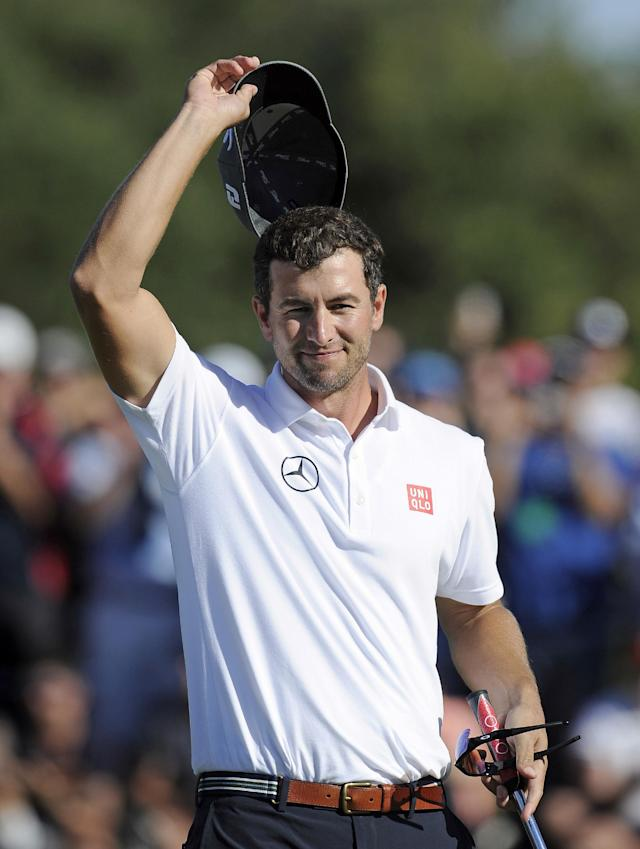 Adam Scott of Australia acknowledges a crowd as he celebrates on the 18th green after winning the Australian Masters golf tournament at Royal Melbourne Golf Course in Melbourne, Australia, Sunday, Nov. 17, 2013. (AP Photo/Andy Brownbill)