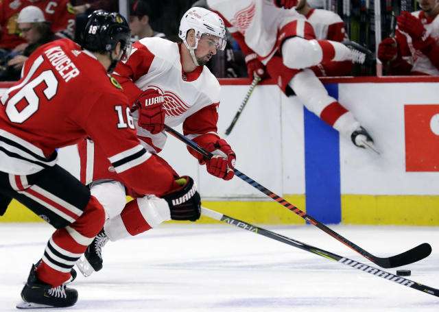 Detroit Red Wings center Dylan Larkin, front right, controls the puck against Chicago Blackhawks center Marcus Kruger, left, during the first period of an NHL hockey game Sunday, Feb. 10, 2019, in Chicago. (AP Photo/Nam Y. Huh)
