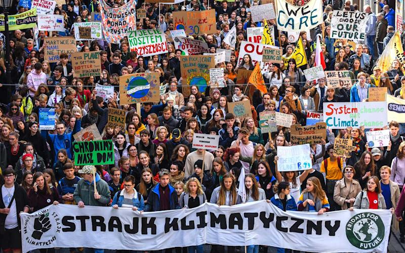 Students, parents and activists march while holding banners and placards during the global climate strike day to demand action be taken on climate change. | SOPA Images/Getty Images