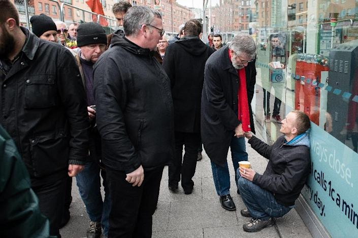 Republican party Sinn Fein leader Gerry Adams (2nd R) shakes hands with a man in Dublin ahead of a general election (AFP Photo/Leon Neal)