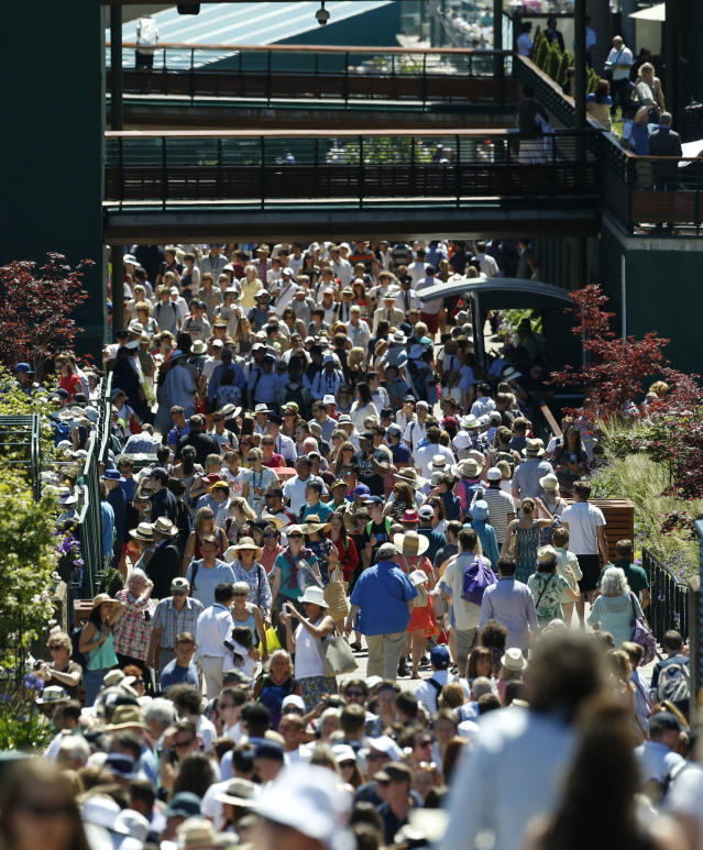 FILE - In this Tuesday, June 30, 2015, file photo, spectators walk around the grounds during the second day of play at the All England Lawn Tennis Championships in Wimbledon, London. (AP Photo/Alastair Grant, File)
