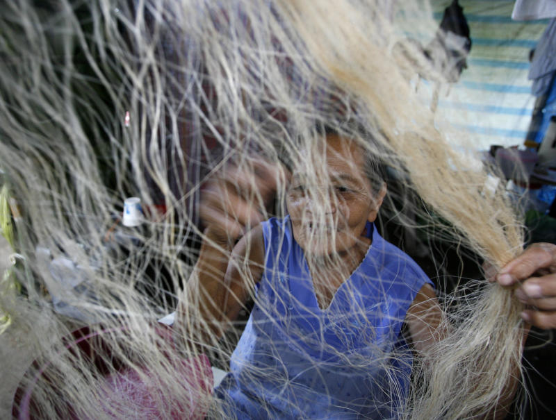 An evacuee sorts out an abaca weave, a major handicraft in the area, at a temporary shelter for villagers living on the slopes of Mayon volcano in San Jose, Albay, about 500 km (310 miles) south of Manila December 19, 2009. Philippine troops evacuated about 12,000 people from villages at the base of the country's most active volcano as it showed signs of a major eruption, officials said on Friday. REUTERS/Erik de Castro (PHILIPPINES)