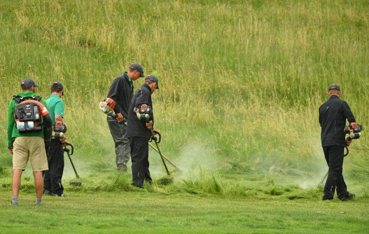 Grounds crew work on the fourth hole during a practice round prior to the 2017 U.S. Open. (Getty)