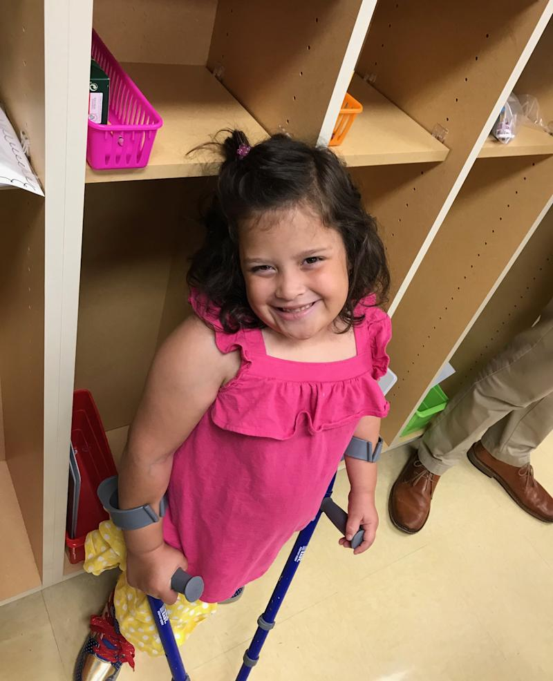 Little girl at school standing with her crutches.