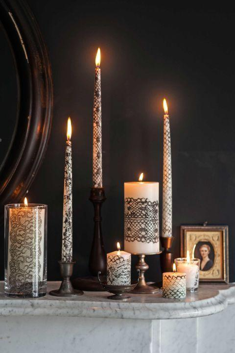 """<p>Wrap black lace around white candles of varied sizes for a hauntingly chic bash. <br><em><a href=""""https://www.countryliving.com/diy-crafts/g1189/best-halloween-crafts-ever/?slide=31"""" rel=""""nofollow noopener"""" target=""""_blank"""" data-ylk=""""slk:Get the tutorial at Country Living >>"""" class=""""link rapid-noclick-resp"""">Get the tutorial at Country Living >></a></em></p><p><a class=""""link rapid-noclick-resp"""" href=""""https://www.amazon.com/Scotch-Vegas-1-42-Inch-5-Yard-2-Roll/dp/B008LAFFK6/ref=sr_1_1?tag=syn-yahoo-20&ascsubtag=%5Bartid%7C10055.g.33437890%5Bsrc%7Cyahoo-us"""" rel=""""nofollow noopener"""" target=""""_blank"""" data-ylk=""""slk:SHOP LACE TAPE"""">SHOP LACE TAPE</a><br></p>"""