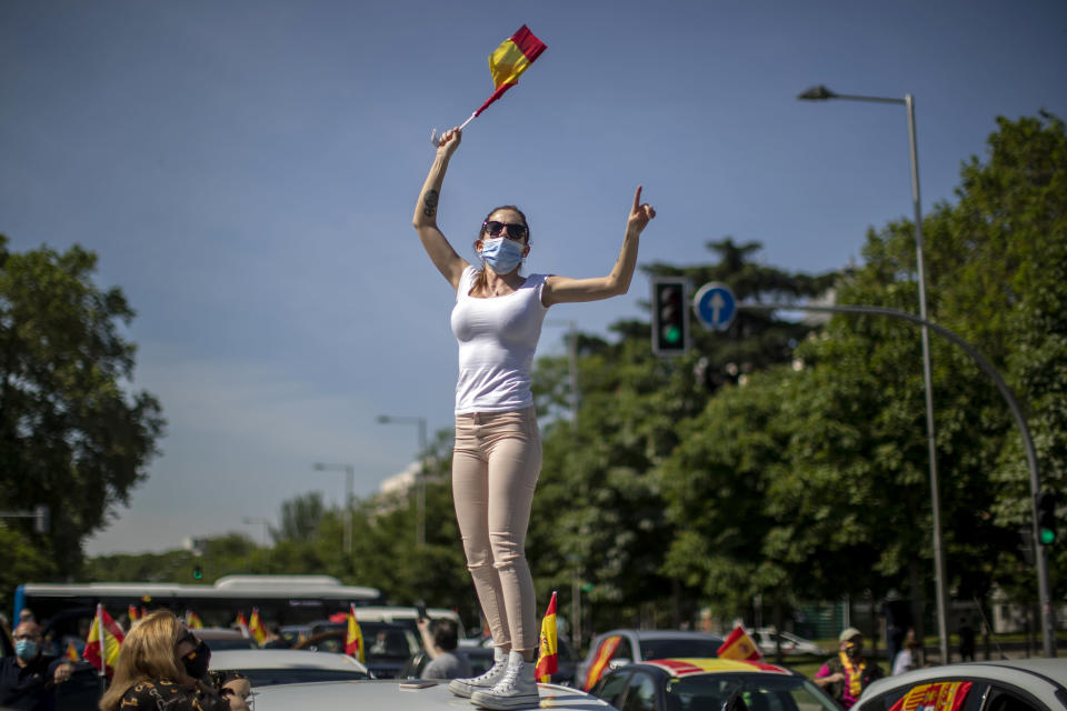 A woman waves a Spanish flag during a drive-in protest organised by Spain's far-right party Vox against the Spanish government's handling of the nation's coronavirus outbreak in Madrid, Spain Saturday, May 23, 2020. (AP Photo/Manu Fernandez)