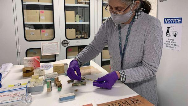 PHOTO: Diane Wendt, a curator at the Smithsonian Institution's National Museum of American History, displays a small glass tube containing one of the original batches of polio vaccine in Washington, D.C., on March 8, 2021. (Ashraf Khalil/AP)