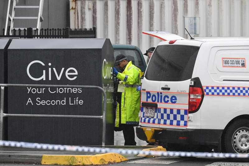 A police van is parked as officers look at a charity bin, where a woman's body was found, near a Burleigh Heads shopping centre.