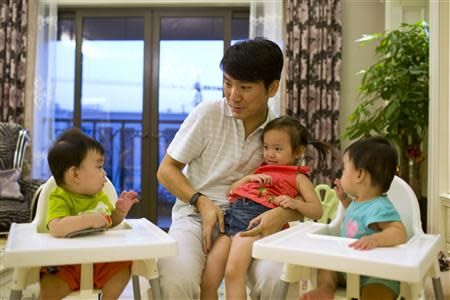 Tony Jiang poses with his three children at his house in Shanghai September 16, 2013. REUTERS/Aly Song
