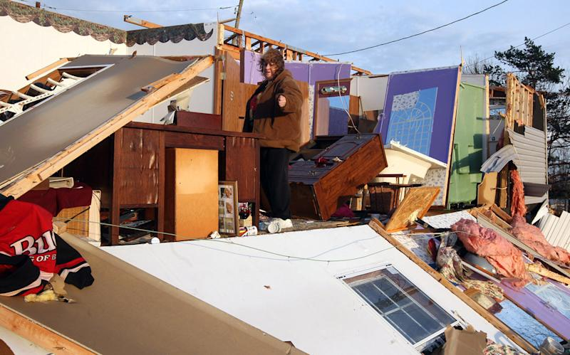 Judy Taylor surveys the damage to her trailer home on Carlisle Road, Piner, KY Friday March 2, 2012 after strong storms ripped through the area about 25 miles south of Cincinnati, OH. (AP Photo/The Enquirer, Patick Reddy)