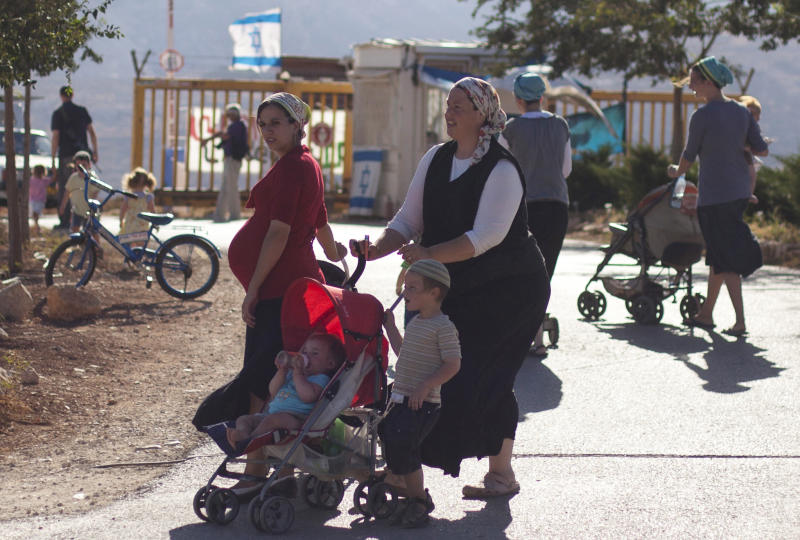 In this photo taken Sunday, Aug. 26, 2012, Jewish settlers are seen in the unauthorized West Bank Jewish settlement of Migron. At first glance, a new legislative proposal seems innocuous enough _ enforcing a uniform labor law that protects all Israeli women, regardless of where they live, against unlawful dismissal. But as with most things in Israel, it comes with an added twist. Critics say that under the guise of woman's rights, the bill's true intent is to further entrench Israeli control over occupied territory. (AP Photo/Sebastian Scheiner)