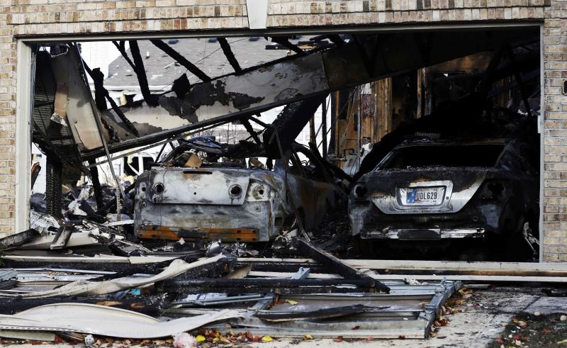 Two cars sit in a home that was heavily damaged by a explosion, Sunday, Nov. 11, 2012, in Indianapolis. Nearly three dozen homes were damaged or destroyed, and seven people were taken to a hospital with injuries, authorities said Sunday. The powerful nighttime blast shattered windows, crumpled walls and could be felt at least three miles away. (AP Photo/Darron Cummings)