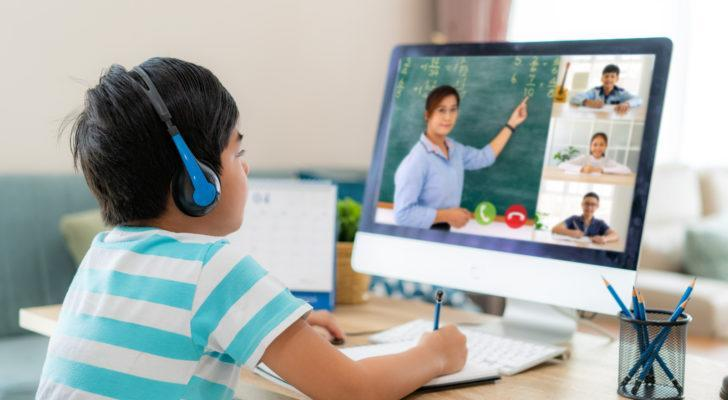 a child takes notes while attending an online class. represents Chinese education stocks
