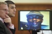 Former New England Patriots football player Aaron Hernandez listens during his trial as defense attorney Charles Rankin (L), looks on while an image of Odin Lloyd is displayed on a monitor in Fall River, Massachusetts, January 29, 2015. Hernandez is accused of murdering semi-professional football player Odin Lloyd. REUTERS/Steven Senne/Pool (UNITED STATES - Tags: CRIME LAW SPORT FOOTBALL)