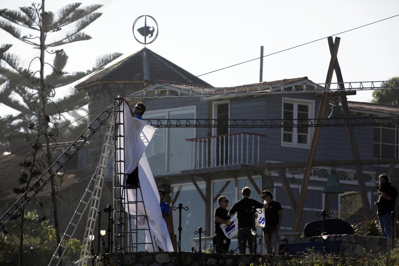 Workers set up protective sheets around the tomb of literature Nobel laureate Pablo Neruda in Isla Negra, Chile, Sunday April 7, 2013. The body of Neruda will be exhumed in an effort to clear up four decades of suspicion about how the poet died in the days after Chile's military coup. (AP Photo / Luis Hidalgo).