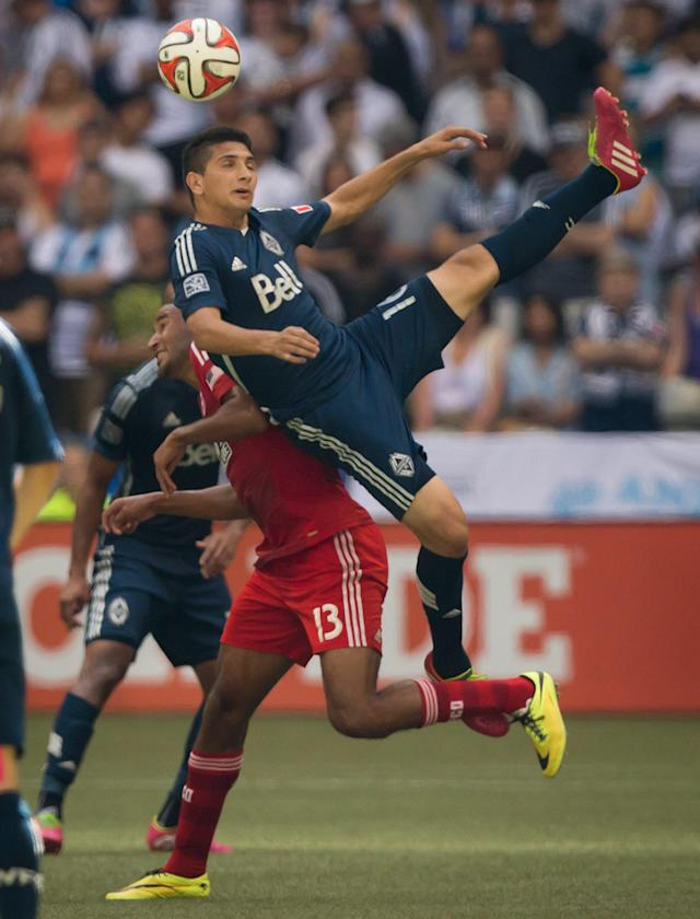 Vancouver Whitecaps' Johnny Leveron, right, of Honduras, falls on top of FC Dallas' Tesho Akindele during the first half of an MLS soccer game in Vancouver, British Columbia, on Sunday July 27, 2014.(AP Photo/The Canadian Press, Darryl Dyck)