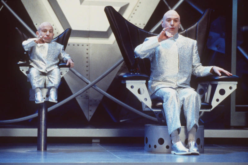 """FILE - In this undated publicity file photo provided by New Line Cinema, Mike Myers, right, and Verne J. Troyer perform in a scene from New Line Cinema's comedy """"Austin Powers: The Spy Who Shagged Me."""" The movie, a James Bond spoof, stars Mike Myers as the sexually charged man of mystery. The """"Austin Powers"""" movies have done the best Bond parodies. (AP Photo/New Line Cinema, K. Wright, HO, File)"""