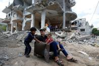 Palestinians sit on chair in front of a building which was damaged in Israeli air strikes
