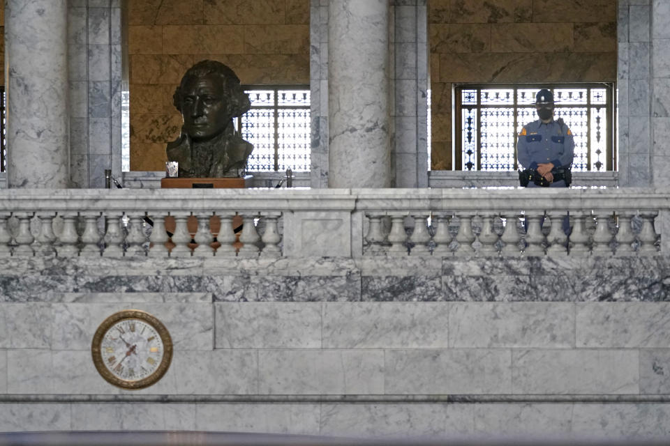 A Washington State Patrol trooper stands near a bust of President George Washington in the Legislative Building, Wednesday, Jan. 13, 2021, at the Capitol in Olympia, Wash. The building is closed to the public, and officials said that security on the Capitol campus will remain tight at least through next week when Joe Biden is sworn in as the President of the United States. (AP Photo/Ted S. Warren)