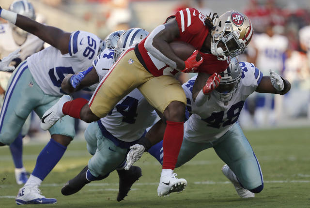 San Francisco 49ers running back Jerick McKinnon, foreground, carries against Dallas Cowboys defensive end Datone Jones (56), linebacker Jaylon Smith, center left, and linebacker Joe Thomas (48) during the first half of an NFL preseason football game in Santa Clara, Calif., Thursday, Aug. 9, 2018. (AP Photo/Josie Lepe)