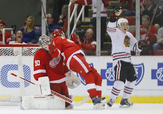 Chicago Blackhawks center Andrew Shaw, right, celebrates Patrick Sharp's goal against Detroit Red Wings goalie Jonas Gustavsson (50), of Sweden, in the second period of an NHL hockey game Wednesday, Jan. 22, 2014, in Detroit. (AP Photo/Paul Sancya)