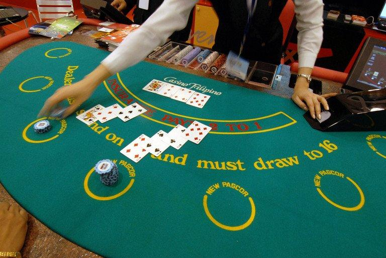 This file photo shows a dealer handing out cards during an exhibit on the gaming industry, in Manila, on March 22, 2007