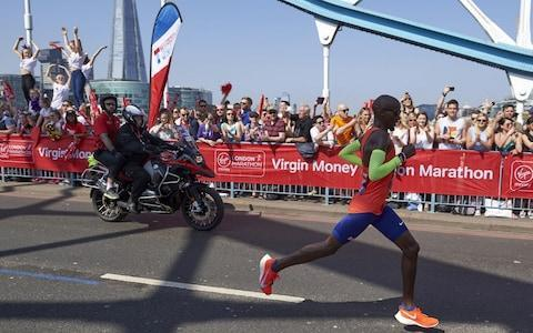 """London Marathon tracker: How to follow running progress Why the first two-hour marathon could be round the corner Kenya's Eliud Kipchoge wins men's race in a time of 2:04:17 Mo Farah finishes third in a British record 2:06:21 Mary Keitany fails in bid to beat Paula Radcliffe's world record Kenyan Vivian Cheruiyot win the women's race in 2:18.31 Britain's David Weir wins men's wheelchair race for eighth time Mo Farah became the fastest marathon runner in British history as he produced a promising and gutsy performance to finish third in his second London Marathon. A """"knackered"""" Farah crossed the line in a time of 2:06:21, comfortably clear of Steve Jones' 33-year-old British record of 2:07:13, despite two mix-ups with water bottles in which he said marathon staff were taking pictures rather than helping him find his drink. The race was won by Eliud Kipchoge, the Olympic champion and the man considered by many to be the greatest marathon runner ever, in a time of 2:04:17. After a stunning start, it had appeared for a while that Kipchoge may be in contention to break the marathon world record, but he was unable to maintain his speed over the final few miles in scorching conditions. Farah, who finished in a disappointing 8th place on his London Marathon debut in 2014, delivered a much-improved performance on his return to the capital's tarmac after three months of intensive training in Ethiopia. Best London Marathon 2018 pictures: The runners, Royals and fancy dress He had vowed to stick with the leaders, no matter the pace, and was true to his word as he remained with the leading pack for much of the race despite Kipchoge leading the contenders in a blistering start. """"They were going for world record pace,"""" Farah said. """"So it was do or die. I went with it and hung on as much as I could. It was ridiculous."""" Mo Farah lies on the floor at the finish with exhaustion Credit: REUTERS The 35 year-old is now fully focused on marathon running after retiring from a track career """