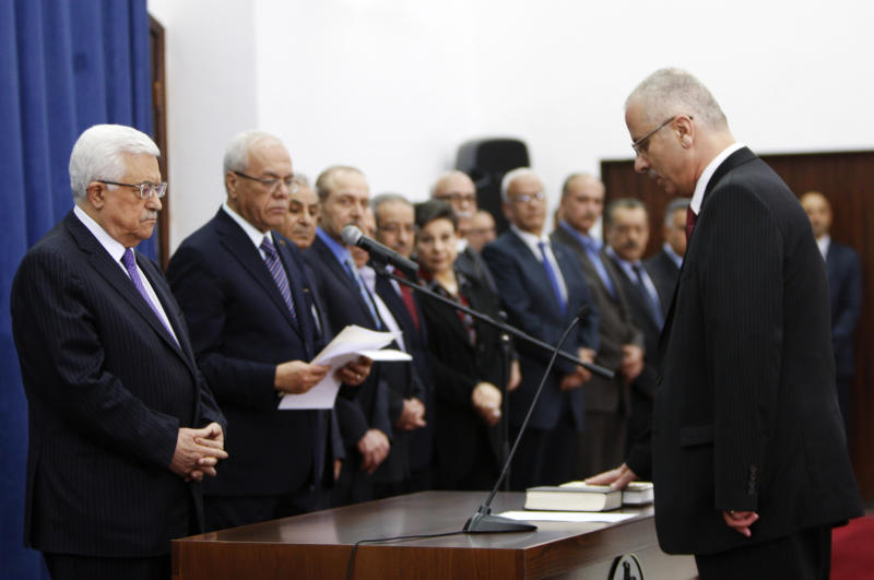 Palestinian Prime Minister elect Rami Hamdallah, right, takes the oath of office in front of the President Mahmoud Abbas as he forms the new government in the West Bank city of Ramallah, Thursday , June 6, 2013. (AP Photo/Majdi Mohammed)