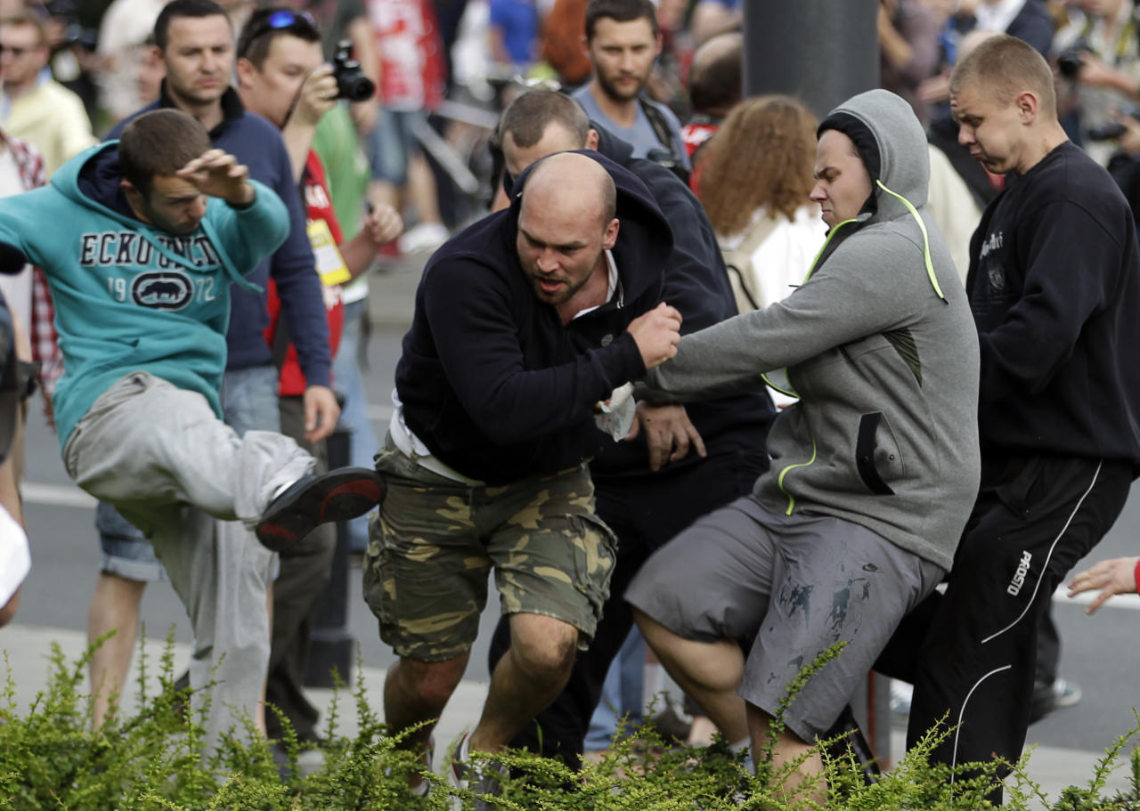 Fans clash prior to the Euro 2012 soccer championship Group A match between Poland and Russia in Warsaw, Poland, Tuesday, June 12, 2012. Russian soccer fans clashed with police and Poland supporters in separate incidents in Warsaw on Tuesday, just hours before the two teams were to meet in an emotionally charged European Championship match. Several people were injured. (AP Photo/Gero Breloer)