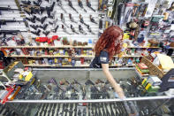 Diane Rowe, owner of Papas Pawn & Gun, disinfects the counter after a costumer came to look at a gun in Grants, N.M., Monday, April 27, 2020. After a year of pandemic lockdowns, mass shootings are back, but the guns never went away. As the U.S. inches toward a post-pandemic future, guns are arguably more present in the American psyche and more deeply embedded in American discourse than ever before. The past year's anxiety and loss fueled a rise in gun ownership across political and socio-economic lines. (Luis Sánchez Saturno/Santa Fe New Mexican via AP, File)