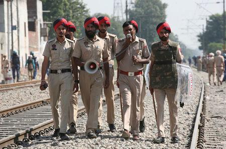 A policeman speaks over a megaphone asking people to stay away from the railway track after a commuter train travelling at high speed ran over a crowd on Friday, in Amritsar, India
