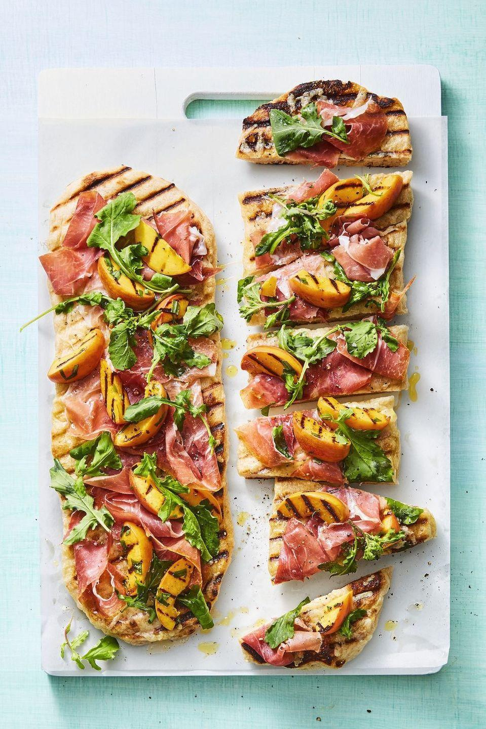 """<p>Who knew everything you needed to make your pizzas taste wood-fired was already in your backyard? Fire up your grill to give these flatbreads a beautiful char.</p><p><em><a href=""""https://www.goodhousekeeping.com/food-recipes/a28468076/peach-and-prosciutto-flatbreads-recipe/"""" rel=""""nofollow noopener"""" target=""""_blank"""" data-ylk=""""slk:Get the recipe for Peach and Prosciutto Flatbreads »"""" class=""""link rapid-noclick-resp"""">Get the recipe for Peach and Prosciutto Flatbreads »</a></em> </p>"""