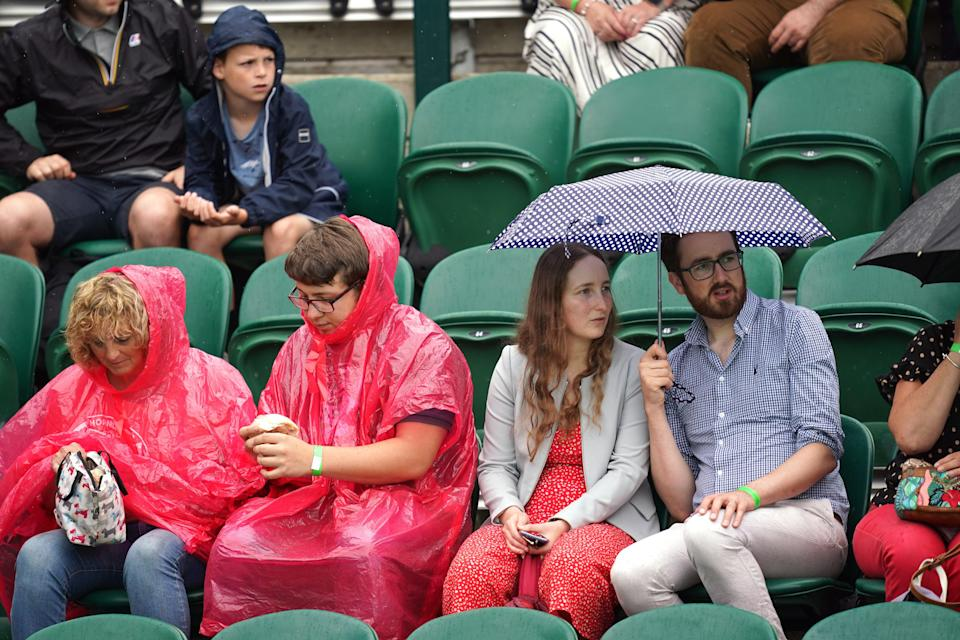 Spectators shelter from the rain on day six of Wimbledon (PA Wire)