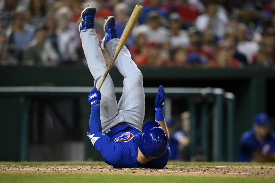 Chicago Cubs' David Bote rolls over after losing his balance while at-bat during the seventh inning of a baseball game against the Washington Nationals, Saturday, July 31, 2021, in Washington. (AP Photo/Nick Wass)