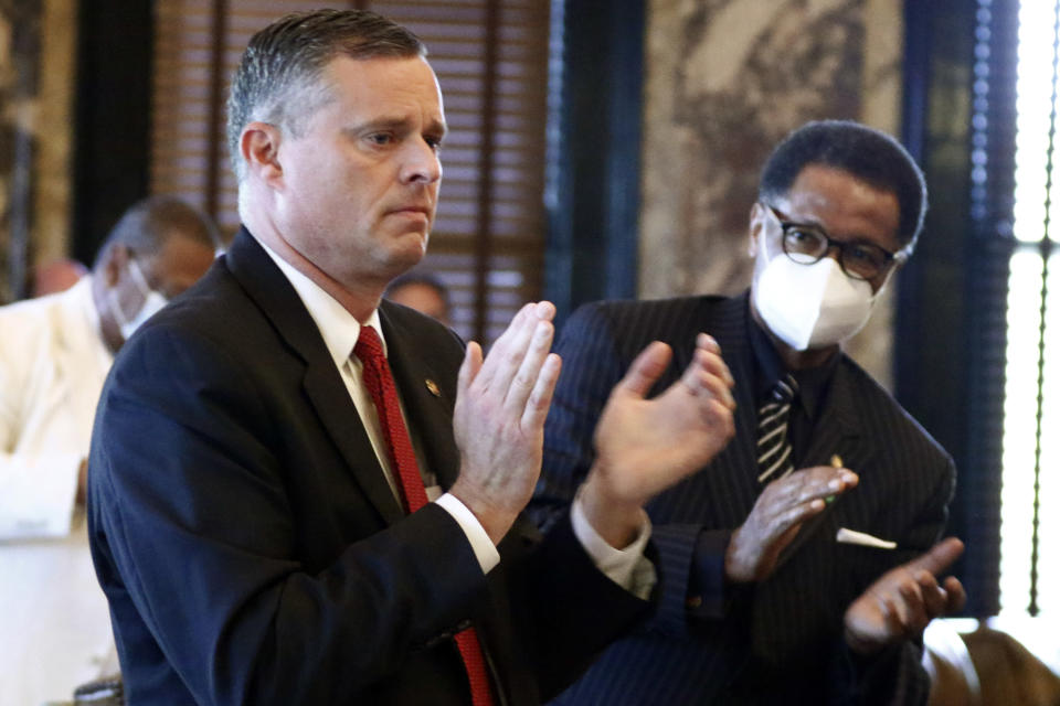Sens. Chad McMahan, left, R-Guntown, and Sollie Norwood, D-Jackson, applaud after the Senate approved legislation to change the state flag, Sunday, June 28, 2020, at the Capitol in Jackson, Miss. Lawmakers voted to surrender the Confederate battle emblem from their state flag. Republican Gov. Tate Reeves has said he will sign the bill. (AP Photo/Rogelio V. Solis)