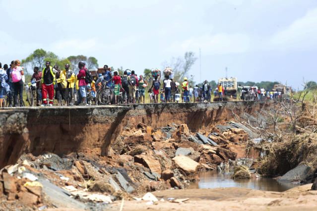 People pass through a section of the road damaged by Cyclone Idai in Nhamatanda about 50 kilometres from Beira, in Mozambique, Friday March, 22, 2019. As flood waters began to recede in parts of Mozambique on Friday, fears rose that the death toll could soar as bodies are revealed. (AP Photo/Tsvangirayi Mukwazhi)