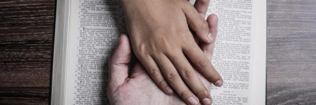 Two hands holding each other on a bible